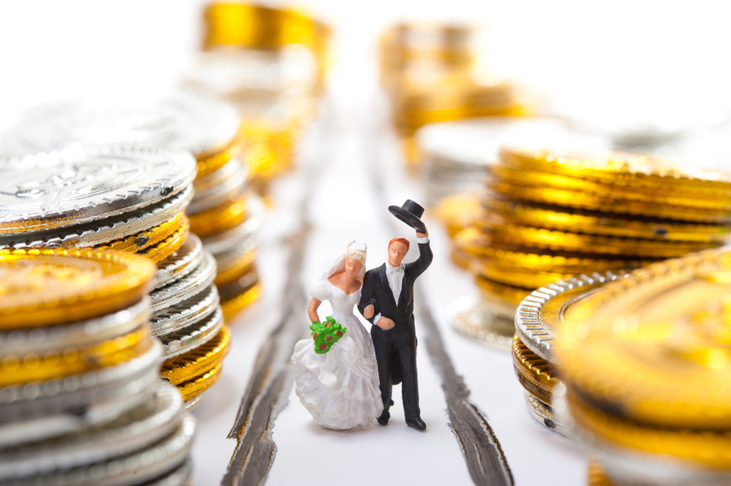 Bride-and-groom wedding cake figurines walking down an aisle lined with stacks of large coins