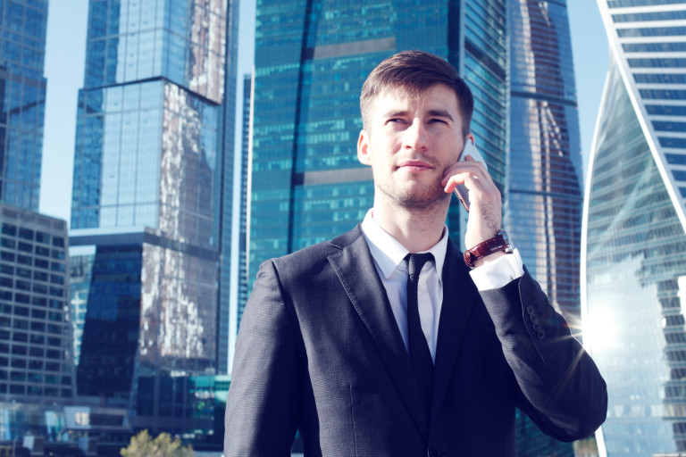Businessman listening on cell phone call while walking through city of modern skyscrapers