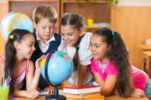 Portrait of cute schoolchildren looking at globe in classroom
