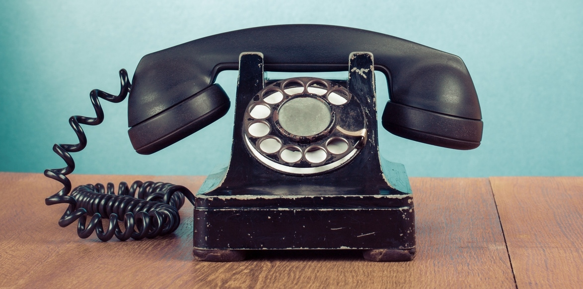 Retro telephone on wooden table in front of turquoise wall