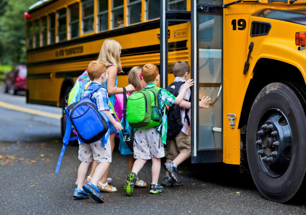 Educational Institutions | young children getting on school bus | Cost Control Associates