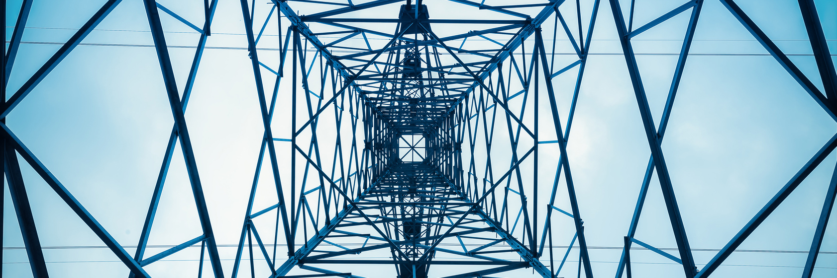 View of electricity tower from the vantage point of standing beneath it and looking up