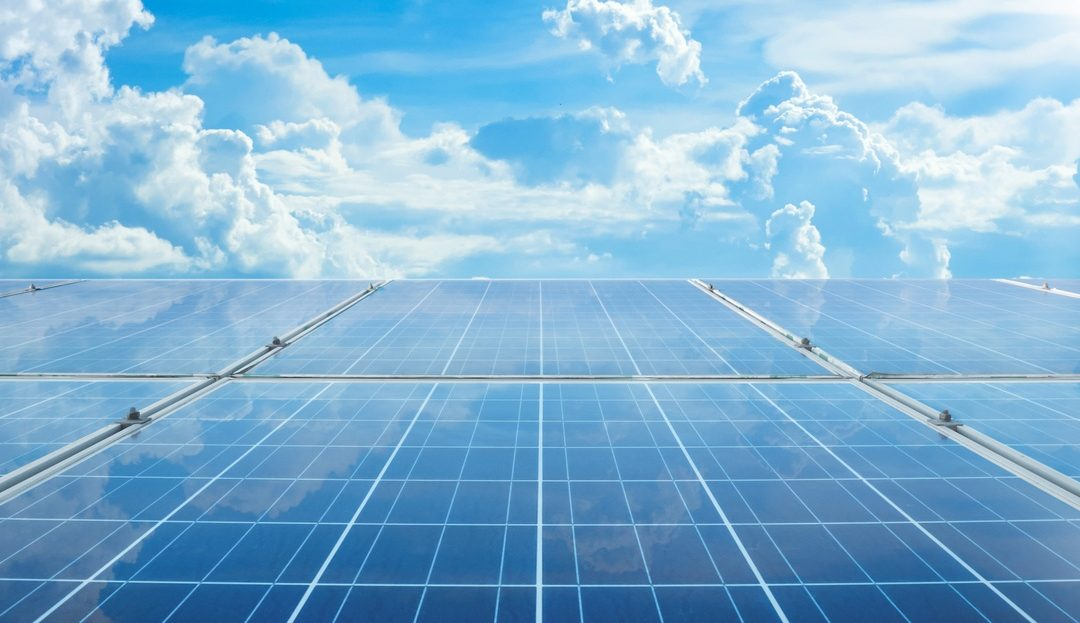 Looking across solar panels to blue sky with clouds above