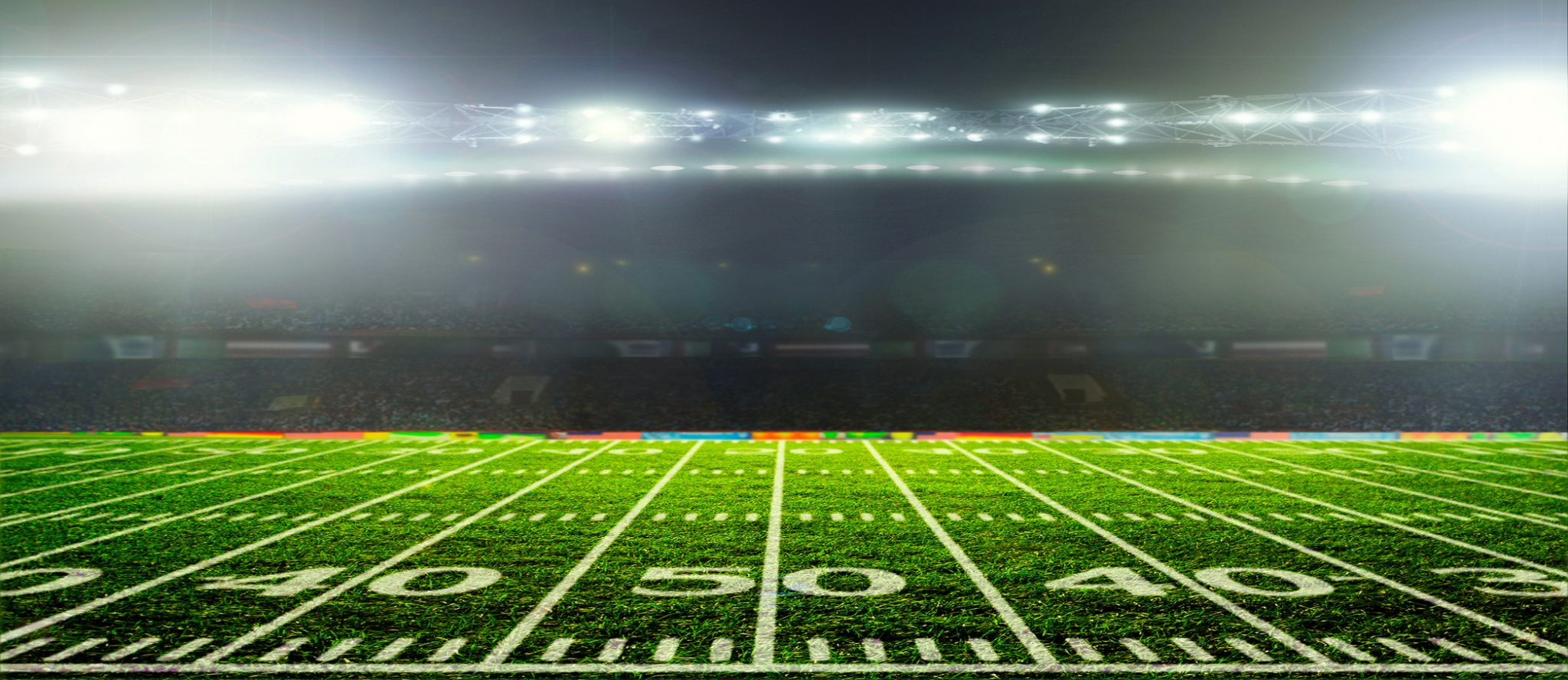 50 yard line of football field with night lights blazing
