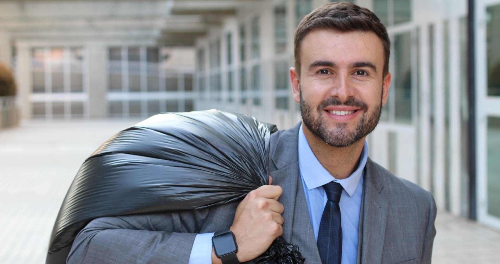 Reduce waste costs at work|Biz man with garbage bag slung over his shoulder