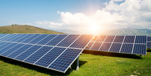 Solar Energy Savings | Solar panels in field with sunrise, mountains