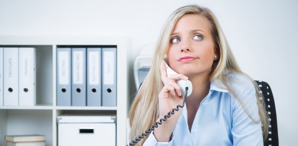 Woman on phone at work looking exasperated from being on hold too long