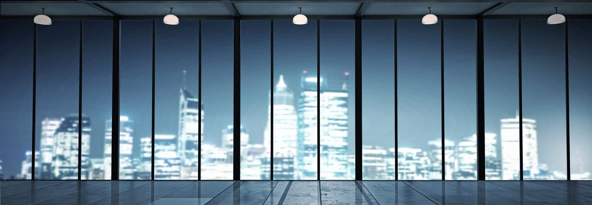 Utility Expense Management Services | empty office space with view of lit up city skyline | Cost Control Associates