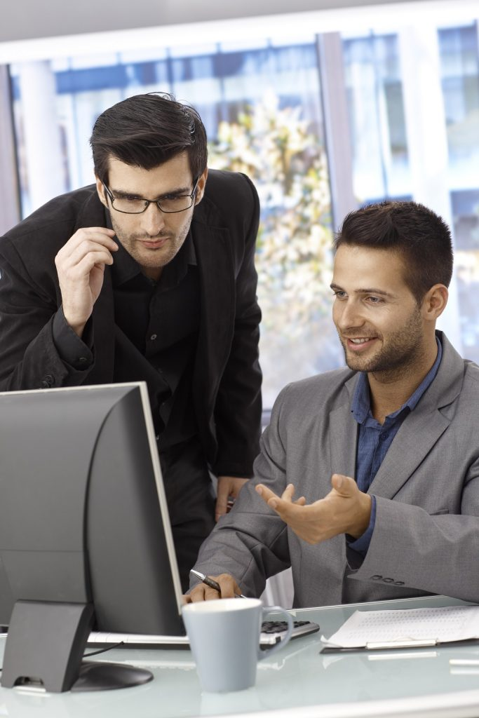 Why Choose Us | 2 business men talking while looking at PC screen | Cost Control Associates