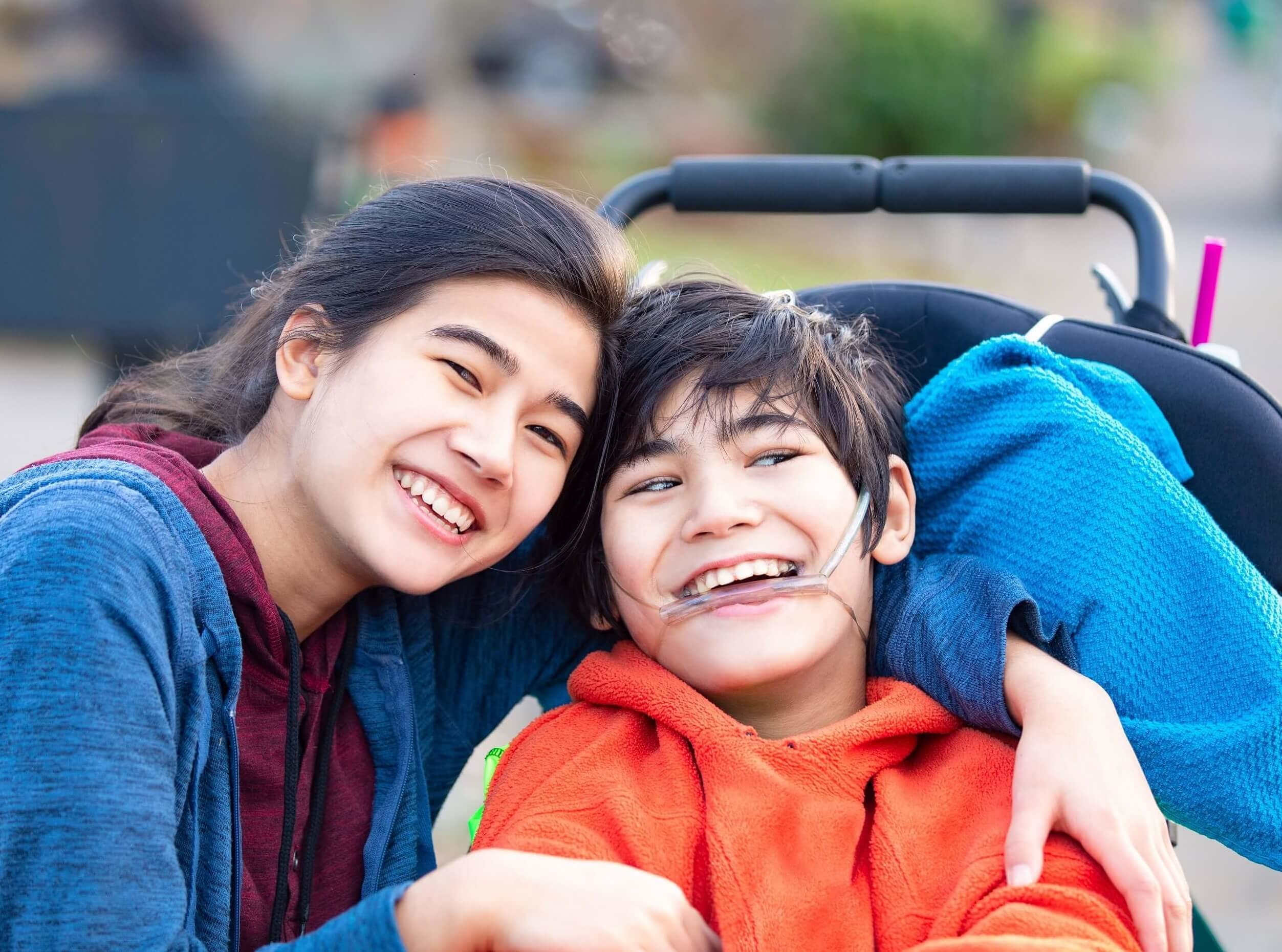 Success Story | Sister hugging smiling brother in wheelchair | Cost Control Associates