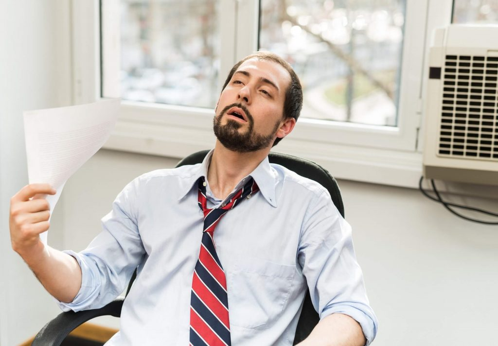 COVID impact on energy pricing   man at desk with fan + AC   Cost Control Associates