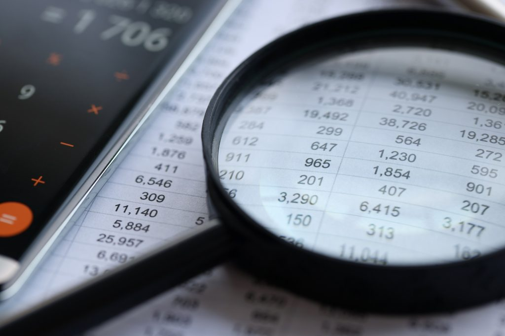 Reduce Business Bank Fees | Magnifying glass atop financial statements | Cost Control Associates